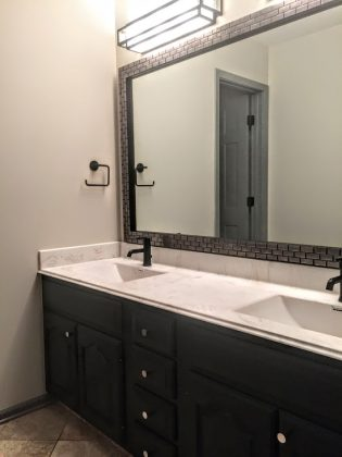 painted existing baninent. Added frame to mirror. New countertop. New faucet and lights. painted